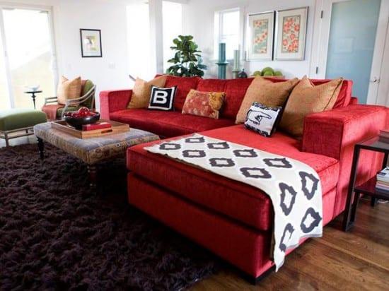 wohnzimmergestaltung mit holzboden und rotem Sofa mit weißer decke-teppich braun
