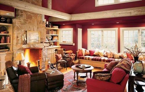 wohnzimmer farbgestaltung- wandfarbe dunkelrot- weiße fensterrahmen-kamit aus naturstein