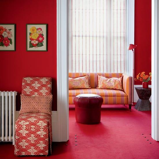 textilboden rot-rote wände mit weißen Türrahmen-sofa gelb-lederhocker rot