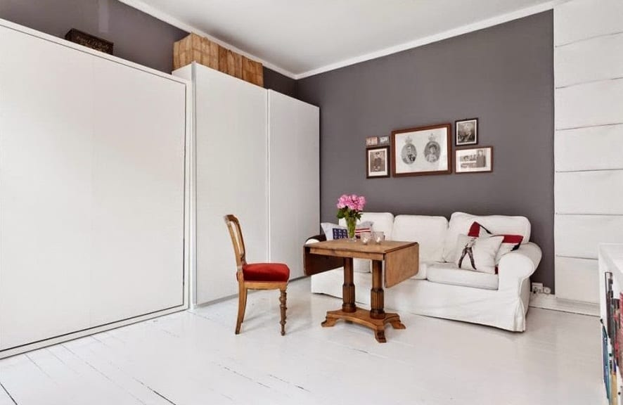 modernes wohnzimmer mit weißem klappbarem bett und holzboden in weiß gestrichen-graue wand mit bilderrahmen dekoriert