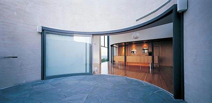 runde terrasse mit natursteinbodenplatten- wohnraum mit gerundetem schiebetür zur terrasse