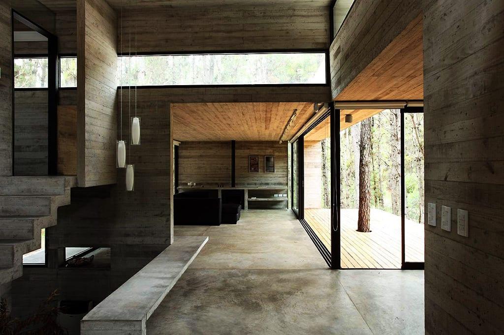 luxus interior mit sichtbeton und bandfenster mit schwarzen fensterrahmen-poliertem betonboden-holzterrasse-betontreppe