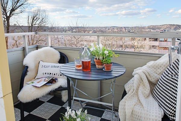 kleines balkon gestalten mit rattanmöbel und schwarz weißen bodenfliesen