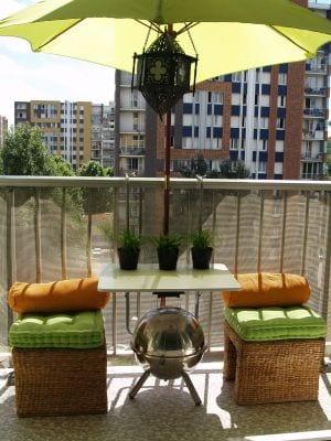 balkon ideen mit rundem BBQ und rattanhockern mit grünen sitzkissen und sonnenschirm grün