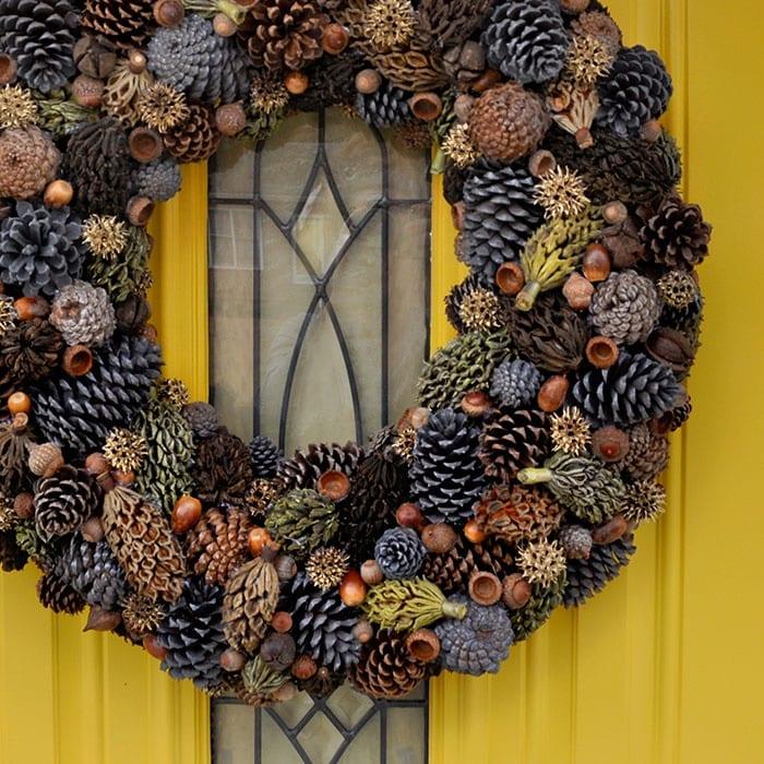 gelbe tür mit kranz aus zapfen dekorieren
