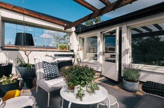 terrasse gestalten mit grauem teppich und weißen runde tische aus metall