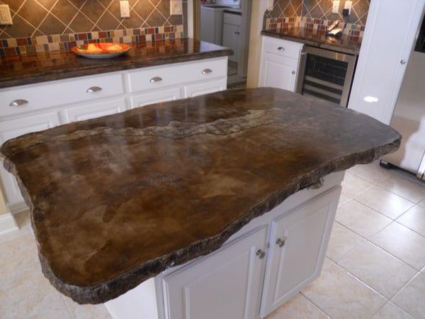 weiße küche mit kochinsel und küchenarbeitspaltten aus beton braun