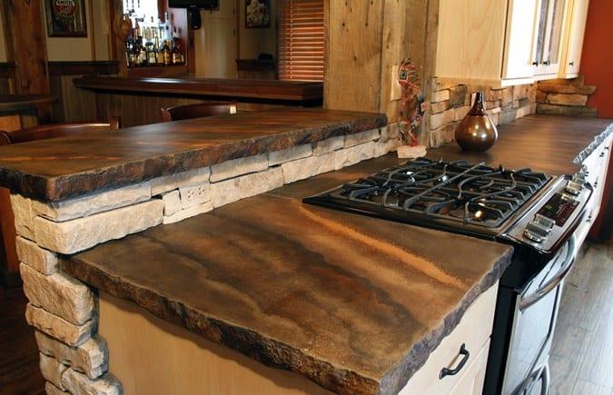 moderne küche mit küchenarbeitsplatten aus Beton braun und natursteinwand weiß