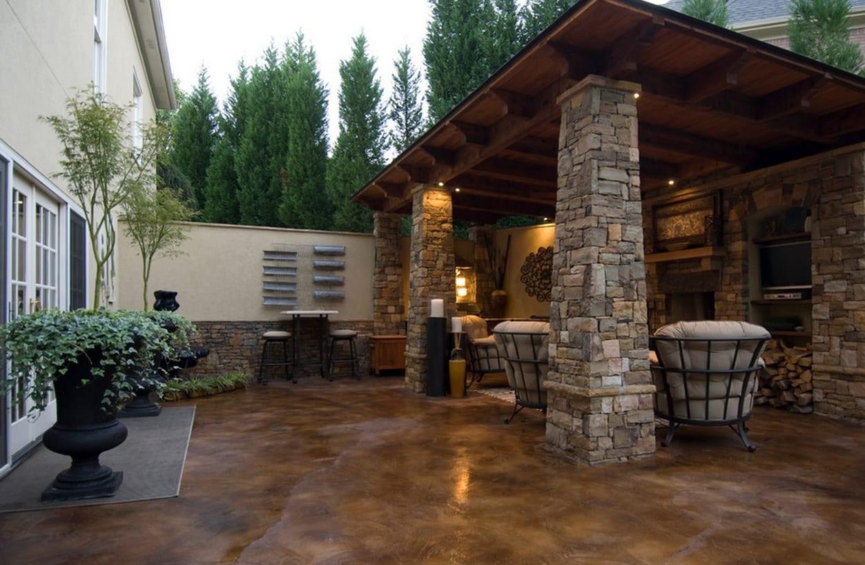 terrassen idee mit betonboden braun und Holzüberdachung-stützen aus natursteinen