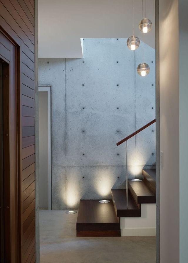 moderne innentrepe mit holzstufen aus dunklem holz und integrierten im treppe bodebbeleuchtung
