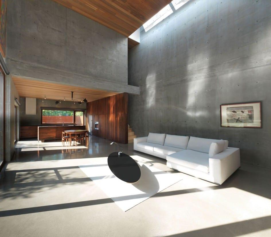 modernes wohnzimmer interior eines betonbaues mit poliertem betonboden-moderne küche aus holz-innentrepe idee mit  holzwandverkleidung-ecksofa weiß mit teppich weiß