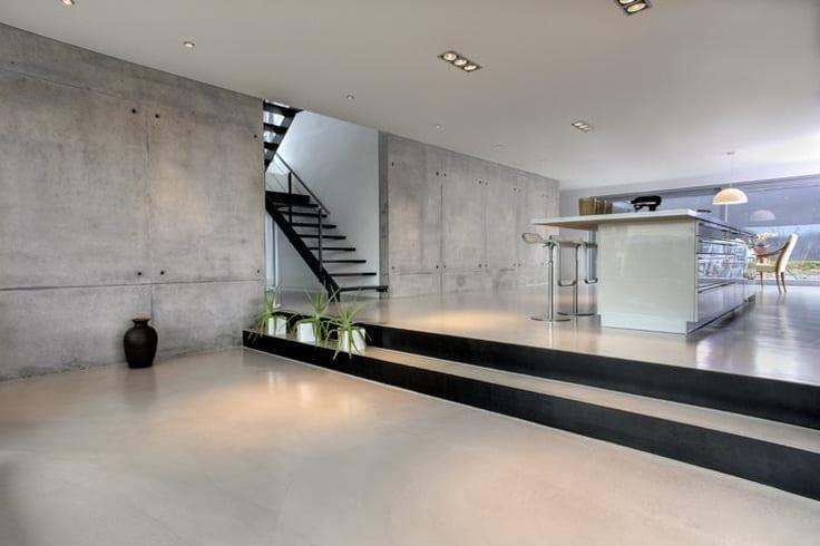 luxus wohn esszimmer mit modernem kochunsel weiß-innentreppe aus schwarzem metall