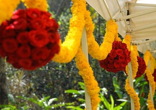 hochzeitdekoration mit Blumengirlanden aus Ringelblumen und Rosenkugeln