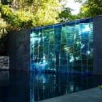 außenwand aus beton mit integriertem glaswand aus blauen glassteinen-gartengestaltung mit teichbecken und modernem wandwasserfall