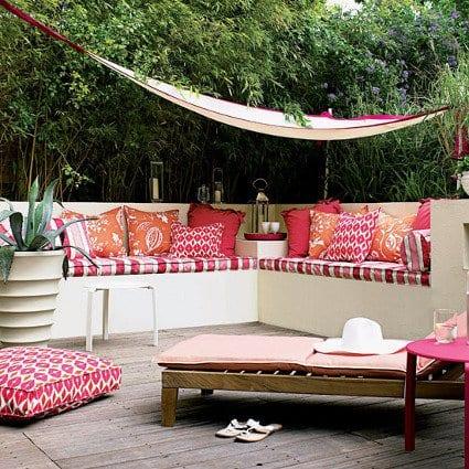sonnensegel terrasse für beschattung von ausgemauerter sitzecke mit roten kissen