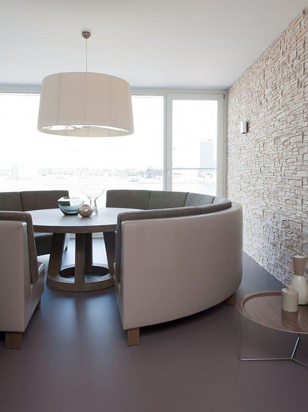 wohn esszimmer mit rundem Esstisch und grauem sofa rund