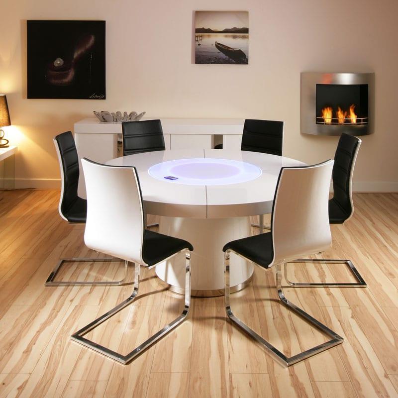 esszimmer mit laminat und runder tisch weiß mit schwarz weißen esszimmerstühlen