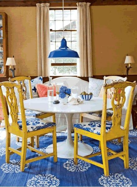 wandfarbe braun und teppich blau mit weißem rundesstisch und gelben holzstühlen kombiniert