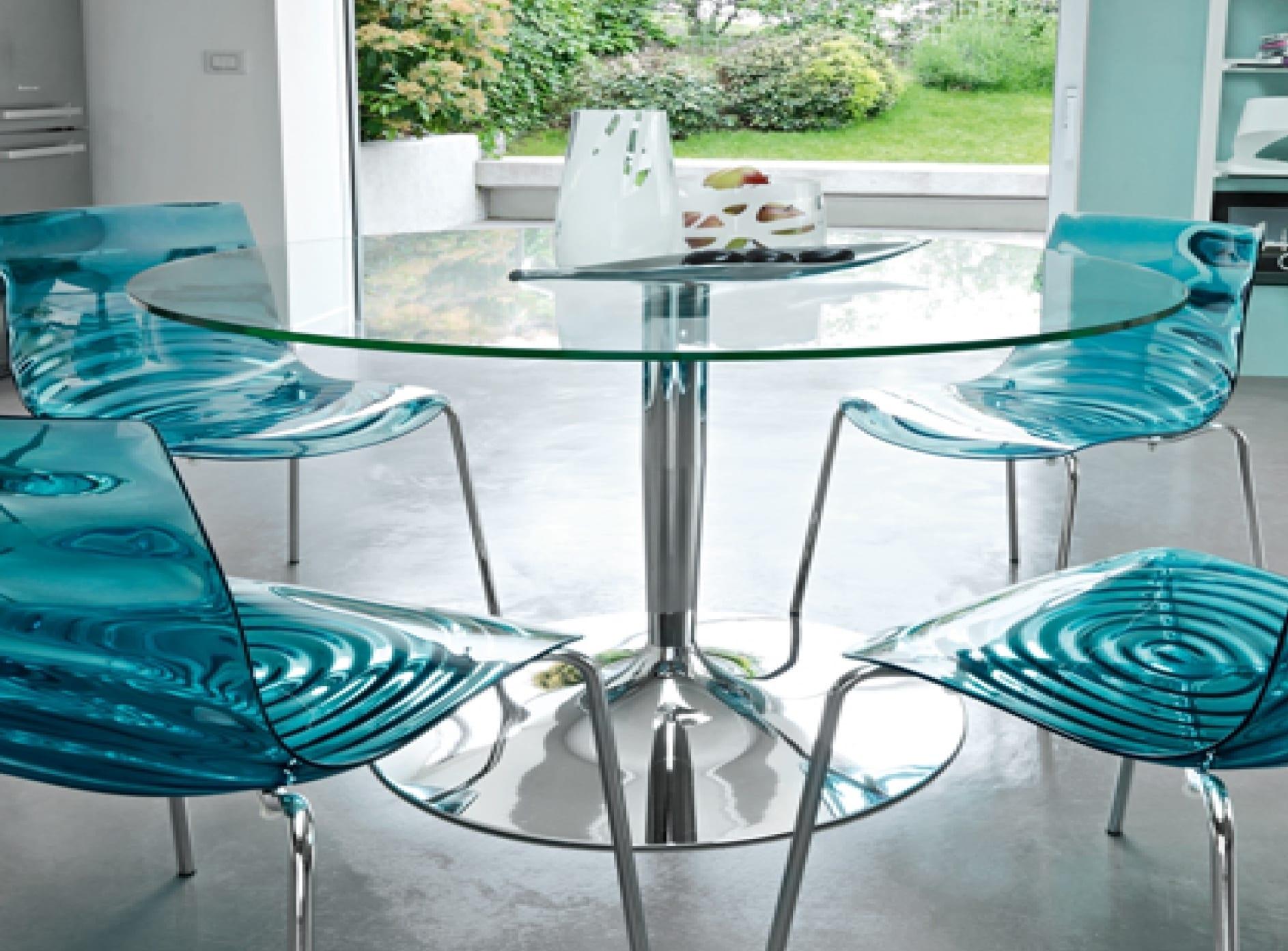 runder tisch mit glasplatte und metalltischbein kombiniert mit blauen esszimmerstühlen aus acrylglas