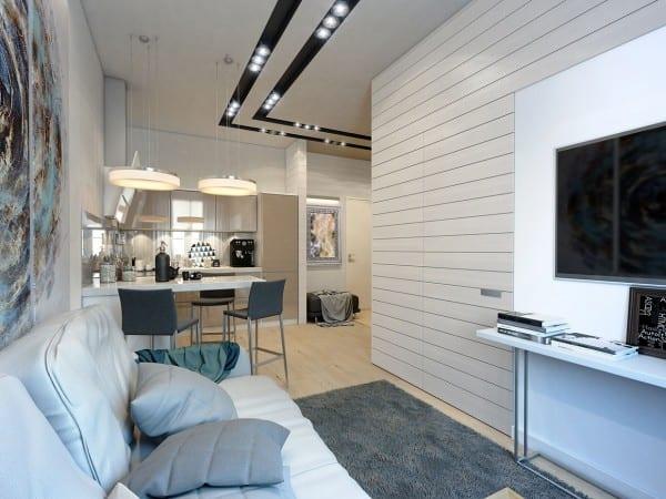 ein kleines appartement mit wohn esszimmer und kleine eckküche mit bar und 3 barhockern grau-weiße wandverkleidung