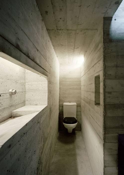 kleine Toilette mit sichtbeton und waschbecken aus beton im wandnische