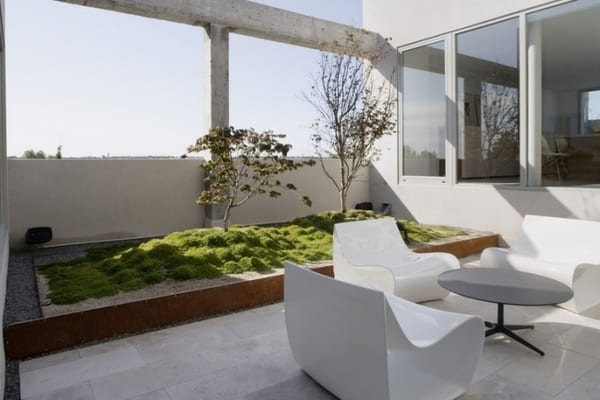 minimalistische terrassengestaltung mit weißen sesseln und terrassenbegrünung