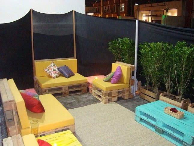 kreative terrassengestaltung mit sichtschutz aus textil und gartenmöbel aus paletten mit gelben sitzkissen