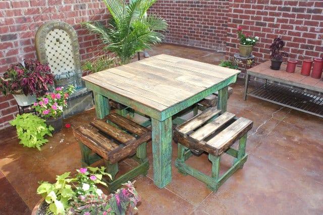 hofgarten mit ziegelamauern und boden aus beton braun eingerichtet mit gartenmöbeln aus paletten