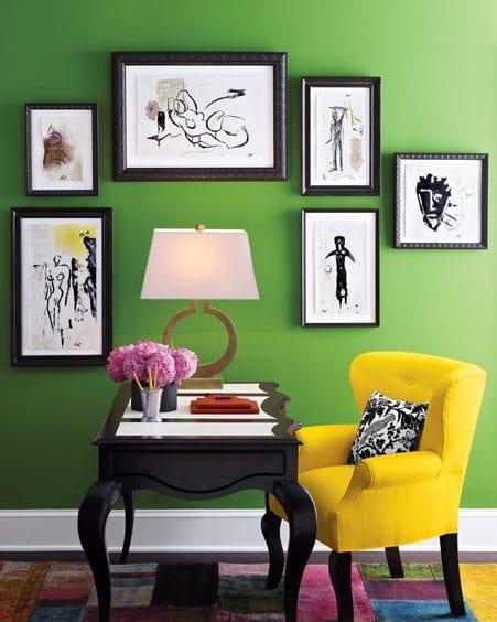 grüne wandfarbe mit schwarzen bilderrahmen- holzschreibtisch schwarz mit polstersessel gelb