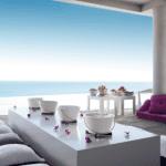 überdachte terrasse mit minimalistischer einrichtung mit weißem couchtisch und weißrn kissen mit BBQ weiß