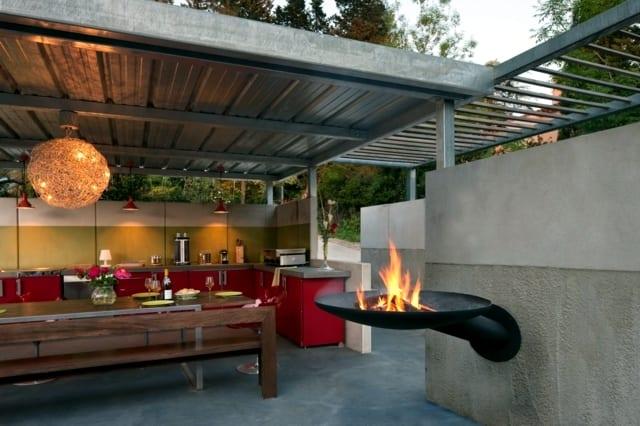 moderne terrassengestaltung mit wandgrill und rote küche mit holzesstisch