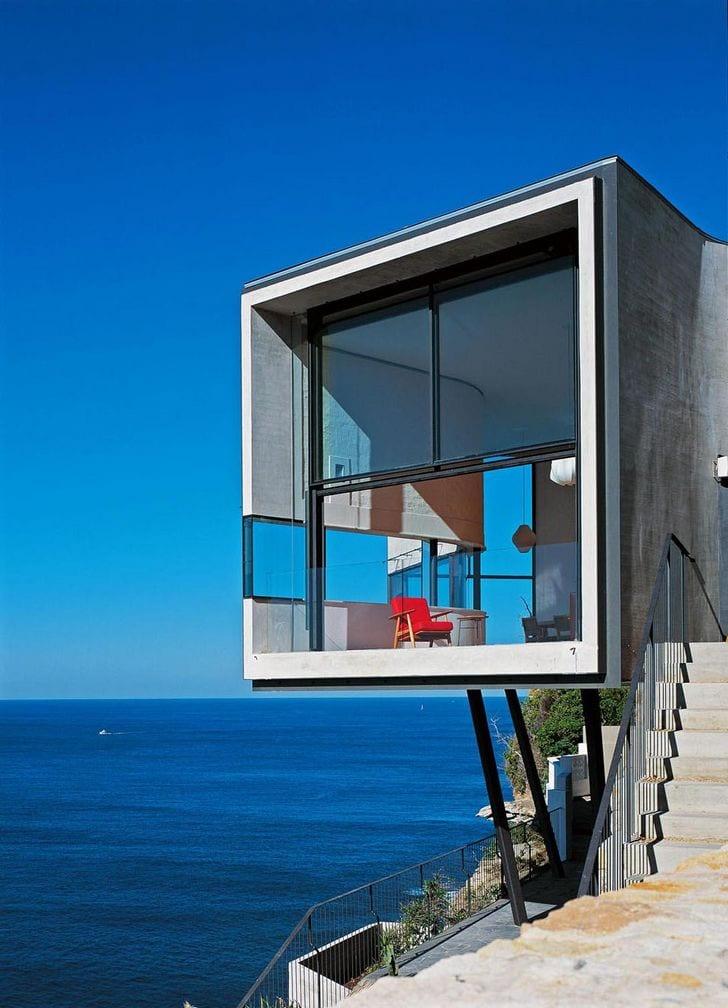 betonhaus auf stützen mit quadratischem panoramafenster