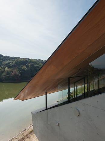 modernes haus aus sichtbeton mit satelldach  und fensterband zwischen außenwänden und dachschräge