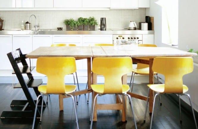 weiße küche gestalten mit holzesstisch und gelben stühlen