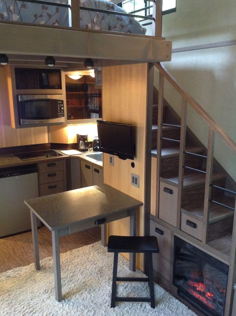 einraumwohnung mit kleiner küche und treppe zum schlafbereich-holztreppe mit eingebauten schubladen