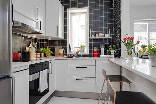 kleine küche einrichten mit schwarzen wandfliesen und weißen Küchenschränken