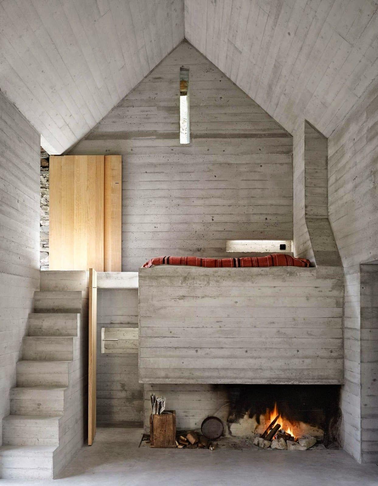 modernes kleines haus aus beton mit offenem kamin und betontreppe