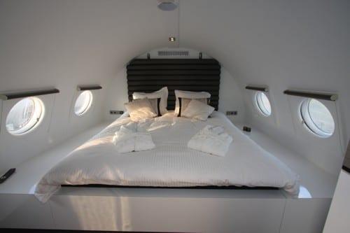 luxus suite mit schlafzimmer weiß und runden fenster-matratze aud weißem podest mit schwarzem kopfbrett