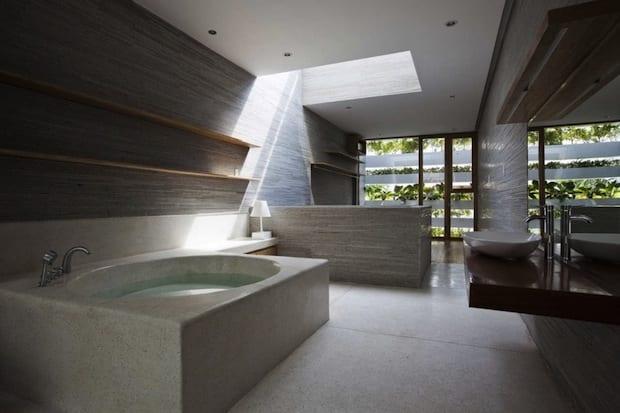 modernes badezimmer interior mit badewanne aus beton und waschtisch aus holz-oberlicht im badezimmer