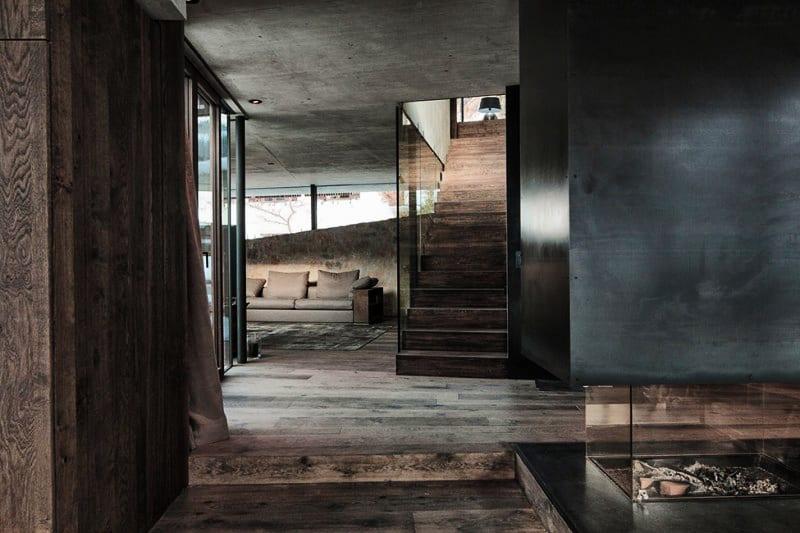 modernes haus aus sichtbeton-luxus wohnzimmer mit holzbodenbelag und kamin aus beton und glas