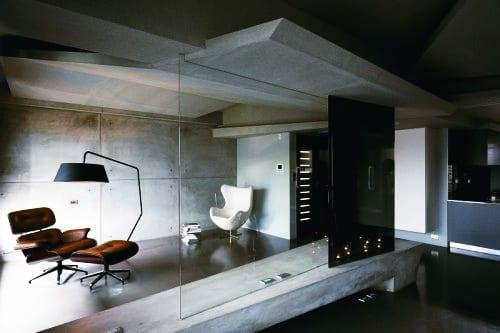 modernes wohnzimmer mit schwarzem boden und sichtbeton-trennwand aus glas