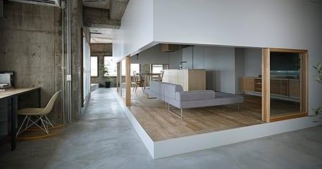 industrialer betonbau mit integriertem neugemautem Wohnzimmer mit holzpodest und schiebefenstertüren mit holzrahmen