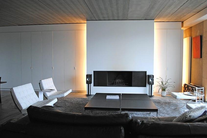 minimalistische schwarz weiße wohnzimmer einrichtung mit kamin und indirekter wandbeleuchtung-eingebaute schränke weiß