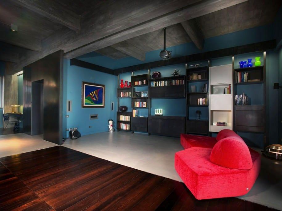 luxus interior mit betondecke und holzboden-wohnzimmer inspirationen mit wandfarbe blau und wandgestaltung mit schwarzen wandregalen-möbelstück polstersessel rot