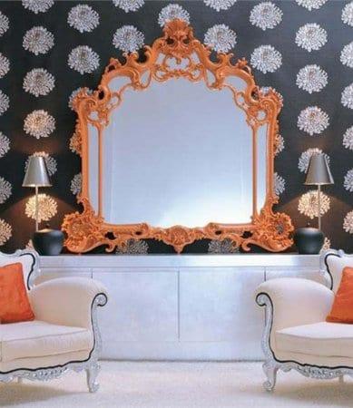 schwarz weiße wohnzimmer inspirationen mit tapete schwarz und sideboard weiß symmetrisch dekorieren-weiße polstermöbelstück mit silbernen füßen und wandgestaltung mit wandspiegel mit orangem spiegelrahmen im barock
