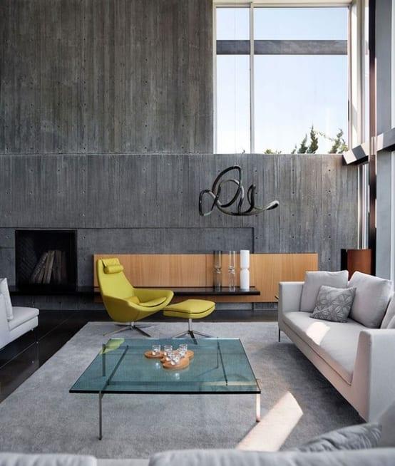 modernes wohnzimmer grau mit wänden aus sichtbeton und eingebautem kamin-traumteppich grau und ledersessel gelb-moderner couchtisch aus glas