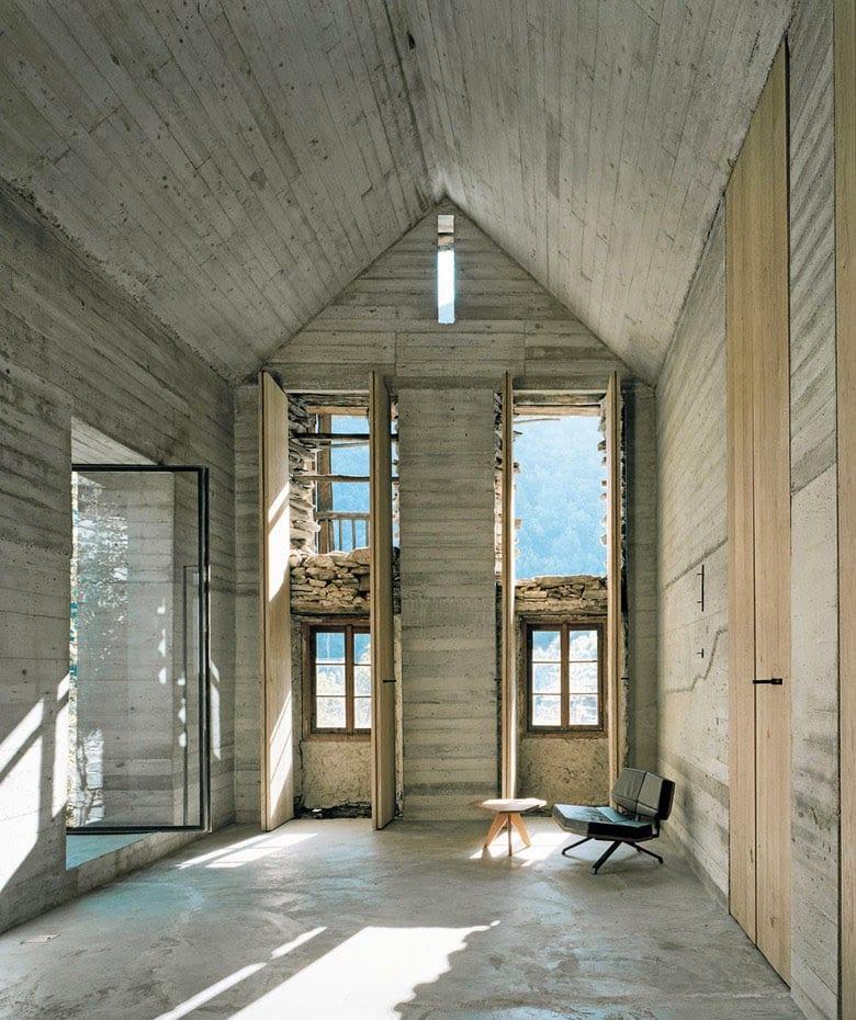 modernes interior mit beton und großformatiger drehtür aus glas-modernes wohnzimmer mit poliertem betonboden und raumhöhe Fenstertüren aus holz
