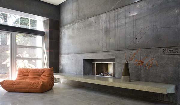 modernes wohnzimmer interior mit kamin und betonregal-poliertem betonboden-polstersessel orange
