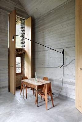 wohnzimmer design mit raumhöhen Holztüren und minimalistische Wandlampe schwarz