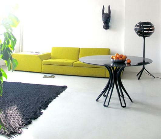 modernes wohnzimmer mit polstersofa gelb und runder Esstisch schwarz